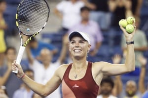Caroline Wozniacki of Denmark hits autographed tennis balls into the crowd after defeating Sara Errani of Italy in their women's quarter-finals singles match at the 2014 U.S. Open tennis tournament in New York